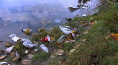 Close view of riverbank littered with trash - stock footage