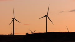 Spinning wind turbines silhouetted against sunset sky Stock Footage