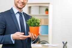 Vivacious office worker holding flower pot - stock photo