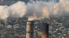 Close-up aerial view of industrial smokestacks emitting smoke - stock footage
