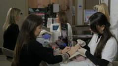 Team of beautiful young female beauticians varnishing customers nails, manicure. Stock Footage