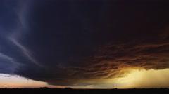 Low dark cloud mass probed by lightning  hangs over dark prairie at sunset - stock footage