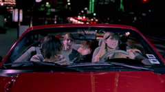 Four teenage girls in a red convertible cruising a city street at night Stock Footage