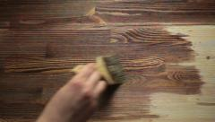 Paint brush painting  wooden table with wood stain Stock Footage