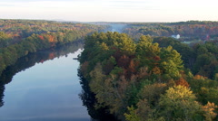Flight over placid river edged in fall colors - stock footage