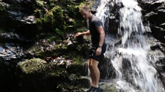 Young man climbs down cliff then jumps into waterfall (HD) Stock Footage