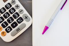 Calculator, notepad and pen on grey background - stock photo