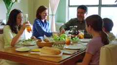 Family sharing a meal at a dining table Stock Footage