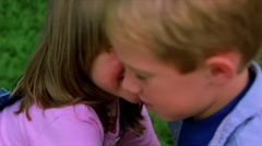 Sister kissing brother forcibly, brother tumbling to sidewalk and laughing Stock Footage
