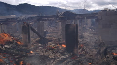 Concrete foundation pillars amid flaming rubble in the aftermath of a structure Stock Footage