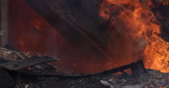 Close view of charred beams, one burning through and bringing down an avalanche - stock footage
