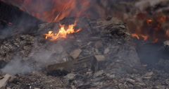 Close-up low flames burning in ash-covered rubble after a structure fire Stock Footage