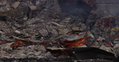 Embers burning underneath a layer of ash amid the rubble of a house fire Stock Footage