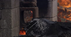 Close-up mound of unrecognizable black rubble in front of flames flickering - stock footage