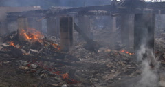 Smoke drifts past smoldering rubble of a house destroyed by fire Stock Footage