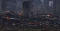 Smoldering charred rubble around the foundation supports of a burned house - stock footage