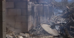 Layered smoldering debris outside a concrete wall of a burned house Stock Footage
