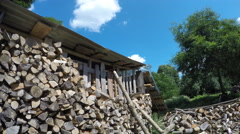 Firewood stack and pile near woodshed and clouds float in blue sky. 4K Stock Footage