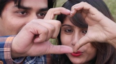 Indian couple making a heart shape towards the camera Stock Footage