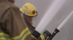 Fireman spraying water from a high pressure hose - stock footage