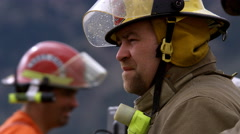 Profile of a firefighter talking to a co-worker at a fire scene Stock Footage