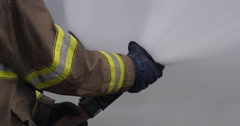 Firefighter's hands adjusting the nozzle of a spraying fire hose - stock footage