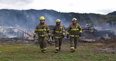 Slow-motion shot of three firemen walking towards the camera with a smoldering - stock footage
