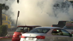 Traffic on Las Vegas Boulevard passing a firefighter hosing down a burning car Stock Footage