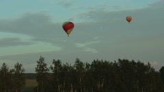 Hot air balloons flying over field in countryside - stock footage