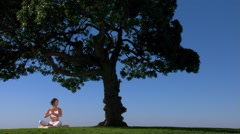 Young woman practicing yoga under a tree Stock Footage