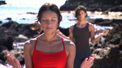 Close view of young woman practicing yoga hand positions, young man in Stock Footage