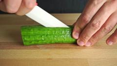 Man cutting cucumber longitudinally Stock Footage