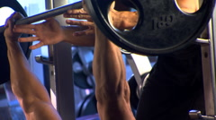 Man doing bench presses in a gym with spotter assisting Stock Footage