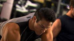 Close view of man leaning on weight bench and doing one-armed rows Stock Footage