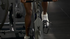 Tilt-up from wheel of stationary bicycle  to woman cycling in spinning class - stock footage