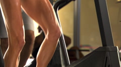 Close-up feet of woman on stair-climbing machine in a fitness club Stock Footage