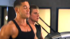 Two men jogging on treadmills, adjusting work-out on computerized display screen Stock Footage