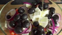 Pouring olive oil on Greek salad in glass bowl. Part of the set Stock Footage