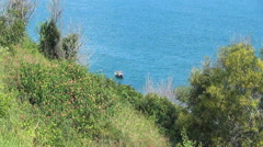 small wooden boat rocking on the waves. Bay is surrounded by greenery. - stock footage