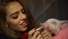 4K beautiful girl with make-up paints lips for pig and gently kisses her Stock Footage