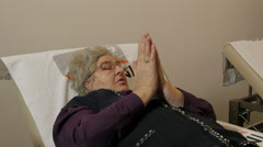 Physiotherapy. Old woman lying in bed and exercising injured wrist, close up. Stock Footage