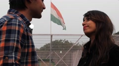 Young Indian couple fooling around in park with Indian flag in background Stock Footage