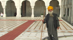 Elderly man in yellow turban standing in courtyard of white-arched building in Stock Footage