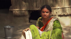 Indian woman in green sari seated near thatched house - stock footage