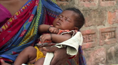 Close-up of Indian mother with sleeping  child in her arms - stock footage
