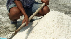 Thai worker seated near mounds of salt Stock Footage