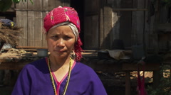 Thai woman wearing traditional costume in front of house raised on poles Stock Footage