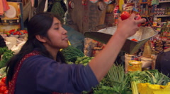 Young Peruvian woman weighing tomatoes at a produce market - stock footage