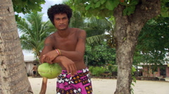 Young Samoan man in lava-lava posed near tropical trees Stock Footage