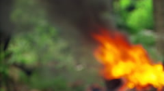 Right pan from soft-focus fire to face of mature Fijian man nearby Stock Footage